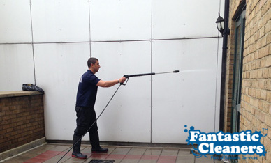 cleaning a wall with pressure washer
